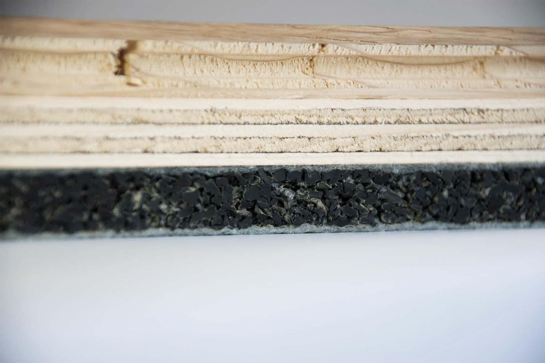 Dettaglio della sezione di un parquet, con un sottostrato fonoisolante e anticalpestio in gomma riciclata